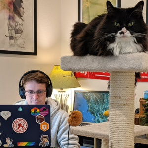 A photo of Josh working from home: he's bundled in a thick hoodie, wearing headphones, and staring intently at his laptop. FlightRadar24 can be seen on a display in the background, and in the foreground? Pico-cat, a floofy tuxedo cat, sits facing the camera atop his cat tree.